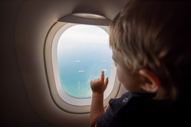 Wiederaufnahme der flüge, konzept der grenzöffnung. ein kleines kind schaut aus dem fenster eines fliegenden flugzeugs auf das meer. erster flug. urlaubsglück. weicher fokus