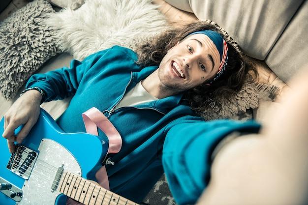 Wiederholung beenden. strahlender gutaussehender kerl, der sein breites lächeln zeigt, während er ein foto mit gitarre auf seinem bauch macht