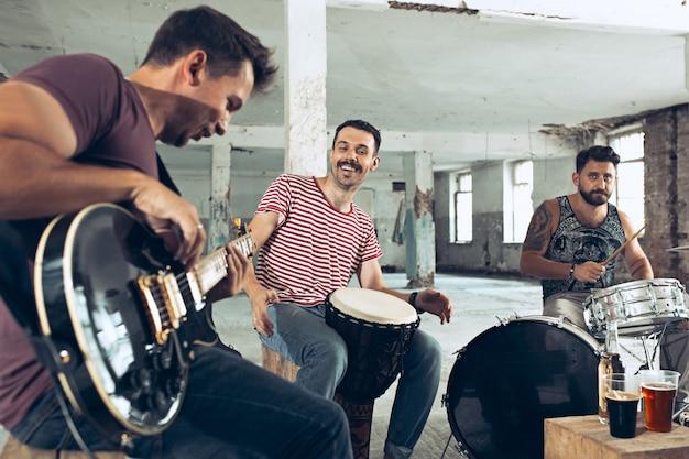 Wiederholung der rockmusikband. bassgitarrist, e-gitarrist und schlagzeuger auf dem dachboden.