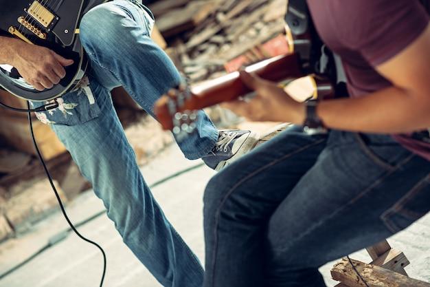 Wiederholung der rockmusikband. e-gitarrist und schlagzeuger hinter dem schlagzeug.