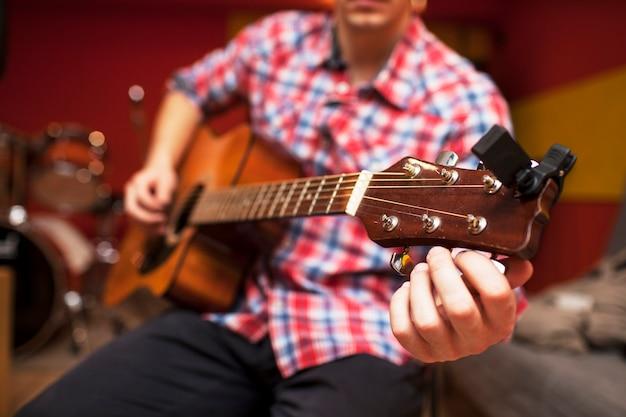 Wiederholung der rockmusikband. geerntetes bild des e-gitarristen und des schlagzeugers hinter dem schlagzeug. probebasis