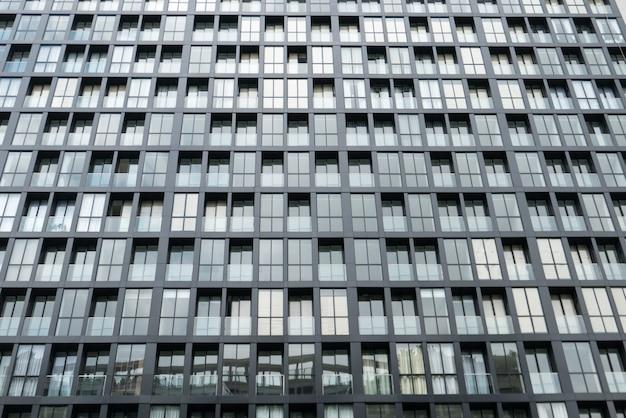 Wiederholungsfensterfassade auf modernem gebäude des hohen aufstieges am sonnigen tag herein in die stadt