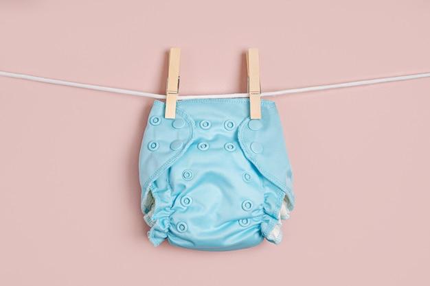 Wiederverwendbare babywindeln aus stoff, die auf einer wäscheleine trocknen. umweltfreundliche stoffwindeln auf rosafarbenem hintergrund. nachhaltiger lebensstil. zero-waste-konzept.