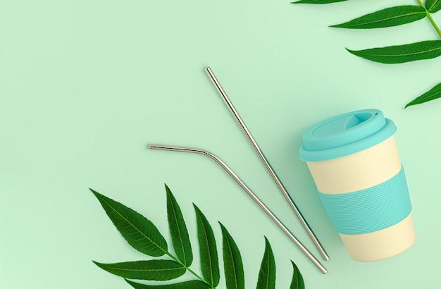 Wiederverwendbare bambus-öko-tasse mit silikonhalter und metallischen trinkhalmen auf grün