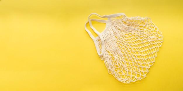 Wiederverwendbare baumwoll-einkaufsschnurbeutel auf leuchtend gelbem hintergrund kopieren sie raum zero-waste-konzept