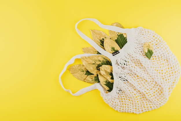 Wiederverwendbare einkaufsnetztasche mit den grünen und goldenen blättern auf gelbem fallherbsthintergrund