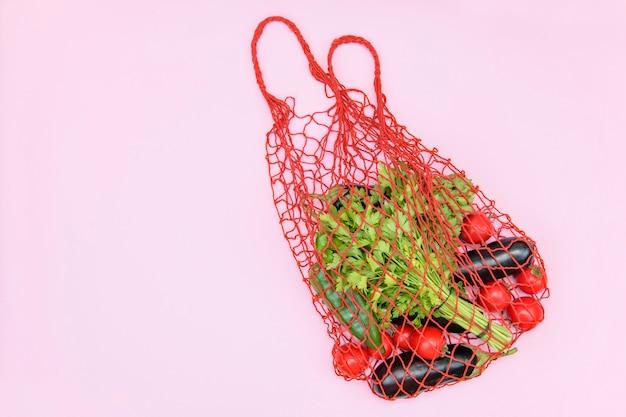 Wiederverwendbare einkaufsnetztasche mit gemüse auf einem rosa hintergrund