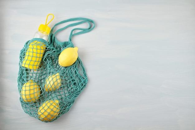 Wiederverwendbare einkaufstasche mit zitronen, früchten und glasflasche