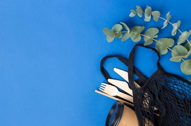 Wiederverwendbare einkaufstasche und eukalyptusblätter an der blauen wand. null-abfall-einkaufskonzept. kein plastik. eco string schwarzmarkttasche mit holzbesteck.