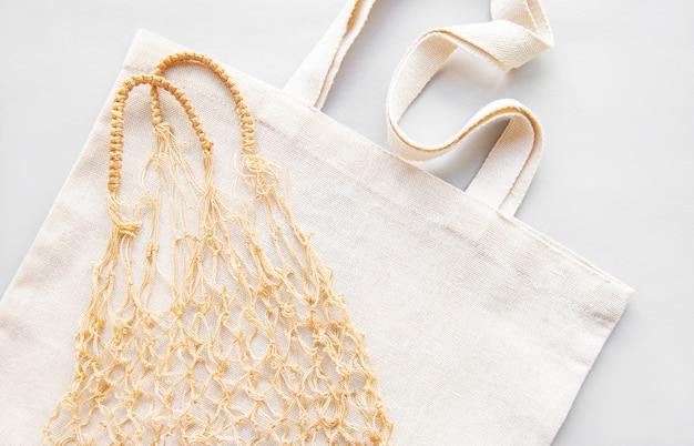 Wiederverwendbare einkaufstaschen auf weiß. ökologisch. draufsicht der maschentasche und der baumwolltasche.