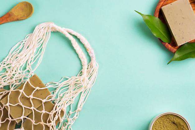 Wiederverwendbare einkaufstaschen mit handgemachter olivenseife, grünen blättern und grünem pulver auf blau. null-abfall-konzept. kein plastik.