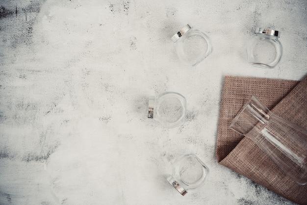 Wiederverwendbare glasflaschen und glas auf hintergrund der rauen oberfläche. nachhaltiger lebensstil. lebensmitteleinkauf und lagerung ohne abfälle