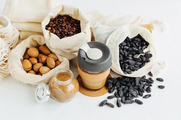 Wiederverwendbare kaffeetasse, produzieren tüten voller nüsse und trockenfrüchte. gläser mit grütze. lebensmitteleinkauf ohne verschwendung. abfallfreies wohnen
