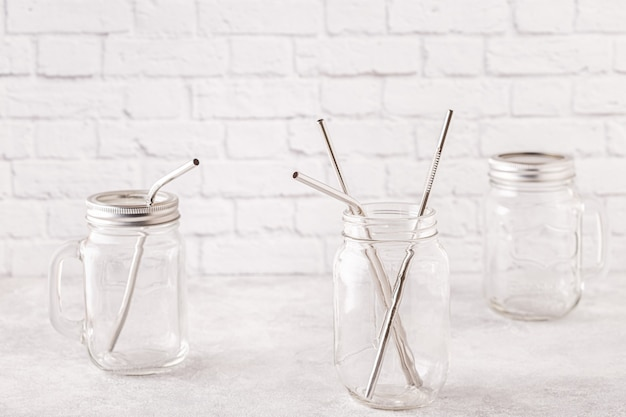 Wiederverwendbare metalltränke und reinigungsbürste in einem glas. null-abfall-konzept.