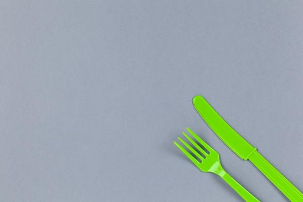 Wiederverwendbare recycelbare grüne gabel, messer aus maisstärke auf grauem hintergrund