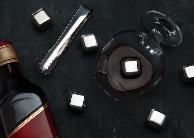 Wiederverwendbare stahlwürfel, die eis simulieren. auf dunklem hintergrund ruderzange, ein glas mit whisky und eine flasche.