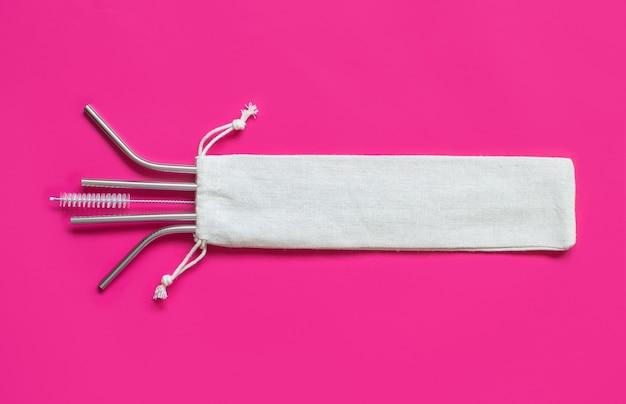 Wiederverwendbare strohhalme aus edelstahl und reinigungsbürste mit cremefarbener baumwolltasche auf rosa hintergrund. umweltfreundliches lifestyle-konzept