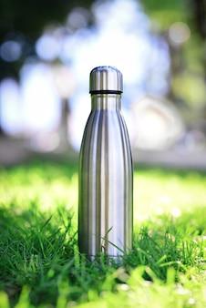 Wiederverwendbare thermo-wasserflasche aus stahl auf grünem gras