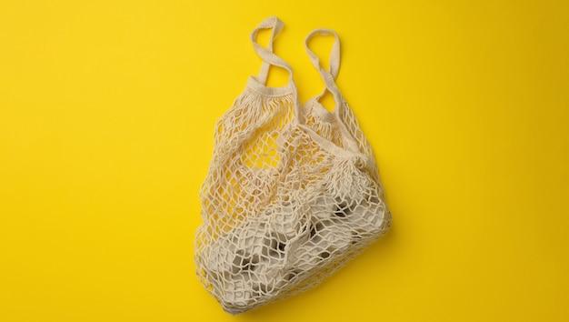 Wiederverwendbare weiße textileinkaufstasche mit eierkartons auf gelbem hintergrund, null abfall, banner