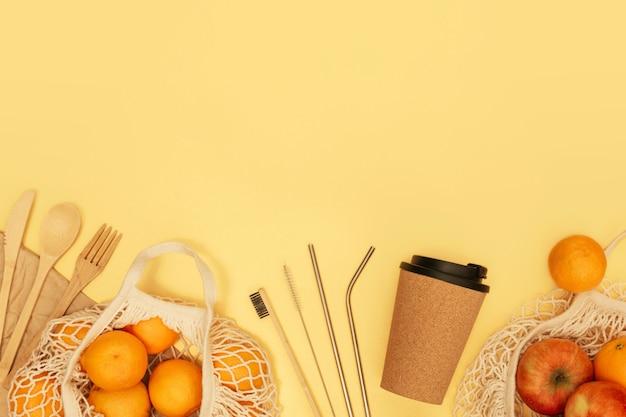 Wiederverwendbares holzbesteck, korkbecher und einkaufstüte mit früchten auf gelbem banner. null-abfall-konzept.