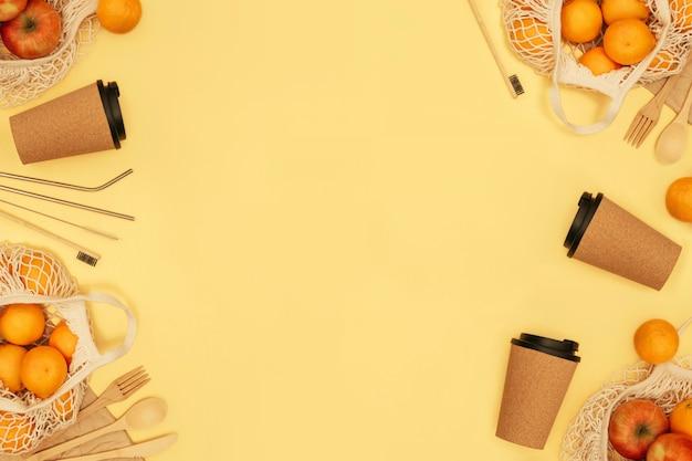 Wiederverwendbares holzbesteck, korkbecher und einkaufstüte mit früchten. zahnbürste und saftschlauch mit bürste, umweltfreundlicher gabel, messer, löffel und stöcken. null-abfall-konzept. copyspace.