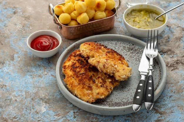 Wiener schnitzel mit kartoffelbällchen und zitronensauce. hähnchenschnitzel in panade