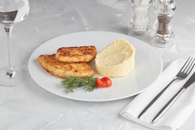 Wiener schnitzel mit kartoffelbrei kartoffeln auf hellem hintergrund