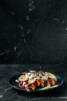 Wiener waffeln auf einem teller mit schokoladenkrümel und bananenscheiben