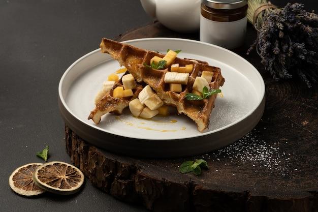 Wiener waffeln mit banane, mango, karamell und minze. klassische belgische waffeln mit heißem dessert