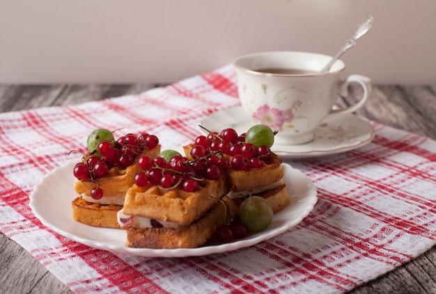 Wiener waffeln mit beeren und einer tasse tee stehen auf einer karierten tischdecke auf dem tisch