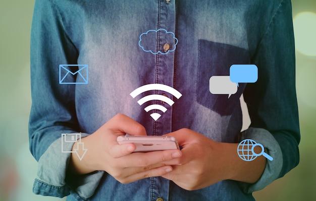Wifi und digitale netzwerkdatenikone über hand unter verwendung des intelligenten telefonhintergrundes