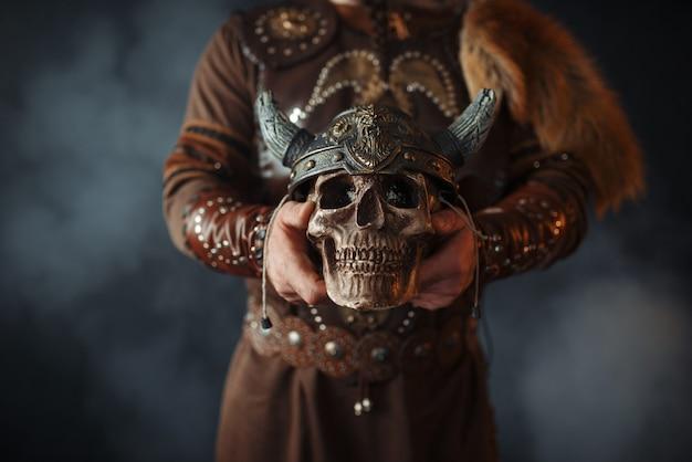 Wikinger in traditioneller nordischer kleidung hält den menschlichen schädel im helm
