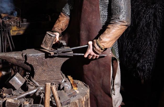 Wikinger schmiedet in der schmiede waffen und schwerter. ein mann in kriegerkleidung ist in der schmiede