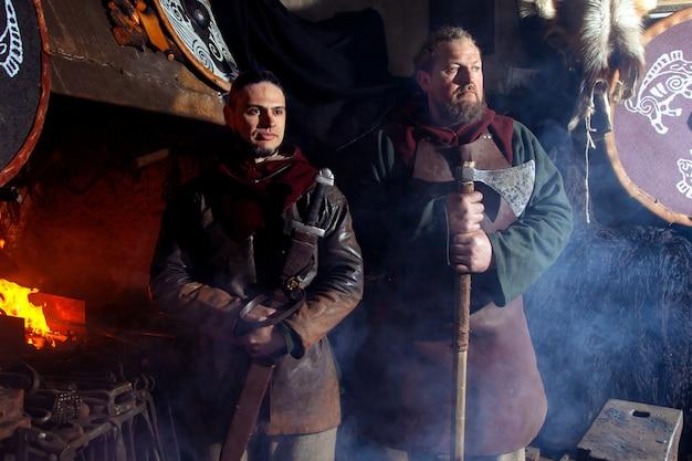 Wikingerschwert griffe schwertständer nachstellung schmiede schmiedekrieger waffe outfit axt schild haut feuer zwei männer