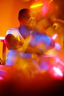 Wild. filmisches porträt eines stilvollen jungen mannes im neonbeleuchteten raum. helle neonfarben. afroamerikanisches modell, musiker drinnen. jugendkultur im party-, festival- und musikkonzept.