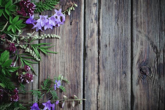 Wildblumen auf dunklem altem holz