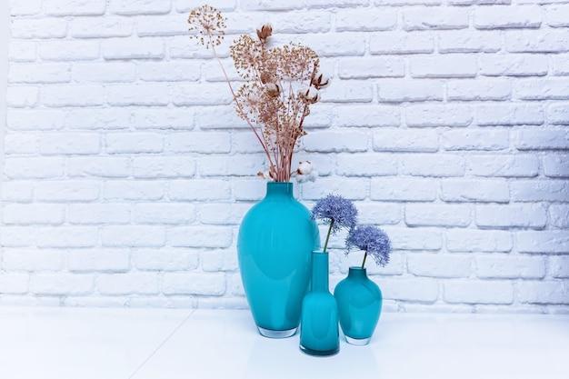 Wildblumen in türkisfarbenen vasen, die auf einem weißen tisch gegen eine weiße kerpwand stehen. wildblumen in einer vase.