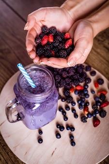 Wilde beeren des frischen selbst gemachten jogurt smoothie in einem glasgefäß auf einer alten weinlese, beeren in den händen, nahaufnahme, draufsicht, vorgewählter fokus, ernte