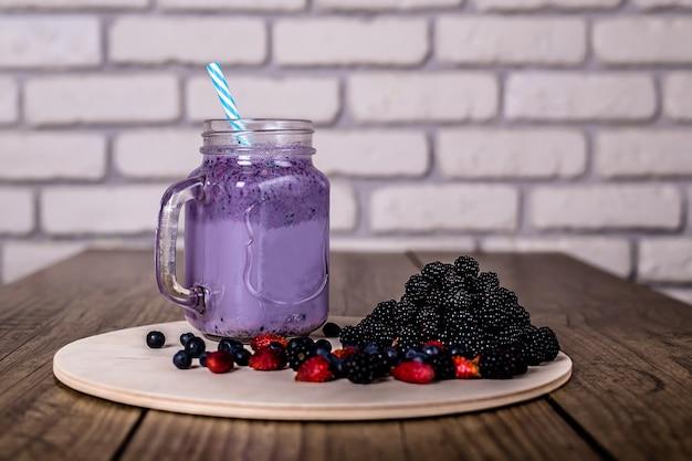 Wilde beeren des frischen selbst gemachten jogurt smoothie in einem glasgefäß auf einer alten weinlese, nahaufnahme, ausgewählter fokus. ernte .