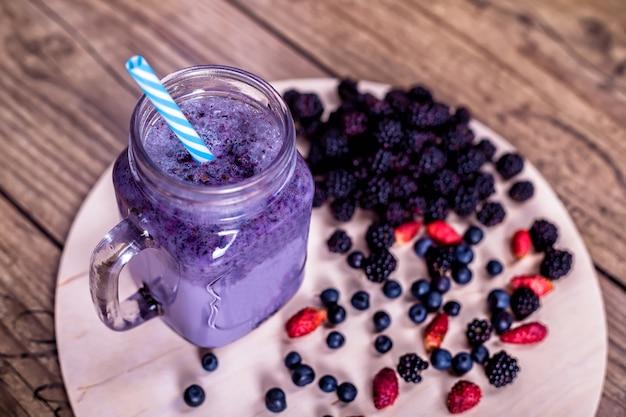 Wilde beeren des frischen selbst gemachten jogurt smoothie in einem glasgefäß auf einer alten weinlese, nahaufnahme, draufsicht, selektiver fokus. ernte .