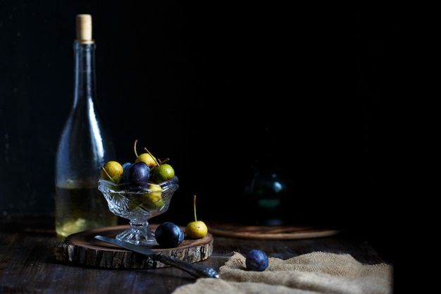 Wilde birne und pflaume in einer glasschüssel und eine flasche hausgemachter birnenwein