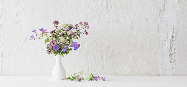 Wilde blumen in weißer vase auf weißer oberfläche