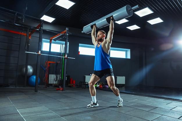 Wilde energie. junge muskulöse kaukasische sportler trainieren im fitnessstudio, machen kraftübungen, üben, arbeiten an seinem oberkörper mit gewichten und hanteln. fitness, wellness, gesundes lifestyle-konzept.