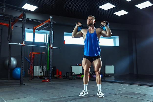 Wilde energie. junge muskulöse kaukasische sportler trainieren im fitnessstudio, machen kraftübungen, üben, arbeiten mit gewichten und hanteln an seinem oberkörper. fitness, wellness, gesunder lebensstil konzept.