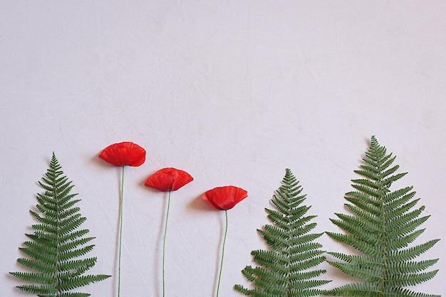 Wilde farne und rote mohnblumen auf stoff