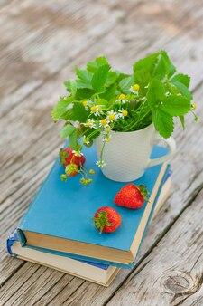 Wilde gänseblümchen und erdbeeren in einer weißen tasse auf büchern auf einem alten rustikalen holztisch