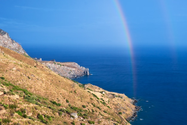 Wilde hügelige küste der insel creta mit einem regenbogen
