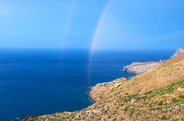 Wilde hügelige küstenlinie von kreta-insel mit einem regenbogen