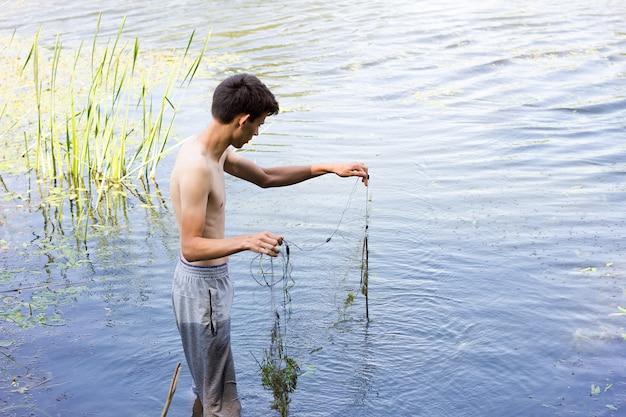Wilderer sammelt netze in der frühlingssaison. wildern auf dem wasser.