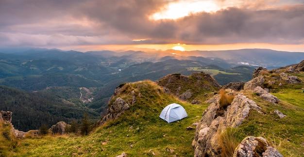 Wildes campen auf einem berggipfel bei sonnenuntergang, schlafen im freien nach der langen wanderung in den bergen